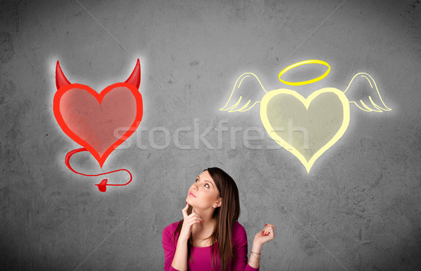 Woman standing between the angel and devil hearts Stock photo © ra2studio