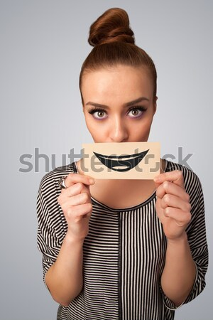 Pretty young girl holding white card with smile drawing  Stock photo © ra2studio