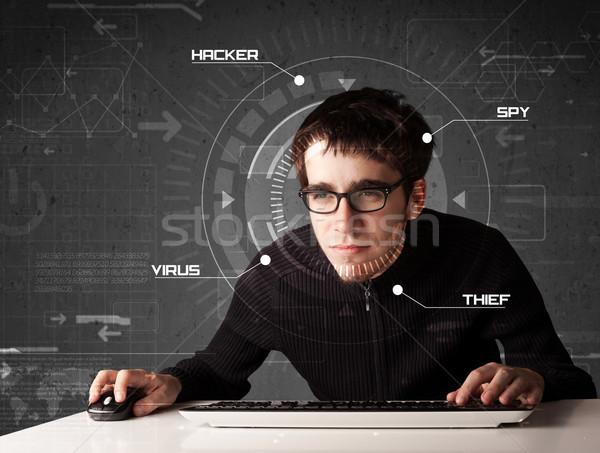 Young hacker in futuristic enviroment hacking personal informati Stock photo © ra2studio
