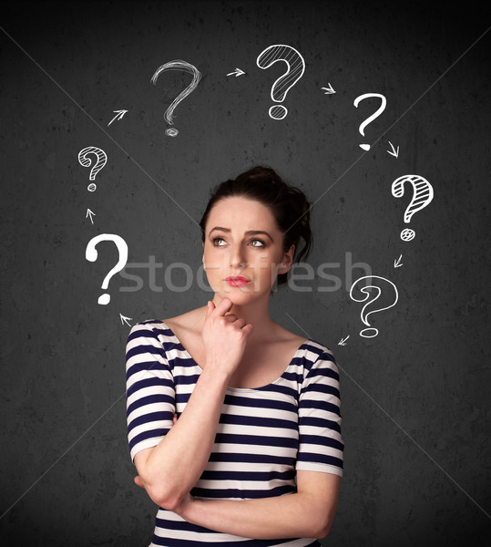 Stock photo: Young woman thinking with question mark circulation around her h