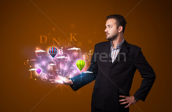 Letters and balloons in the hand of a businessman Stock photo © ra2studio