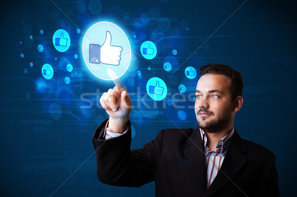 Handsome person pressing thumbs up button on modern social netwo Stock photo © ra2studio
