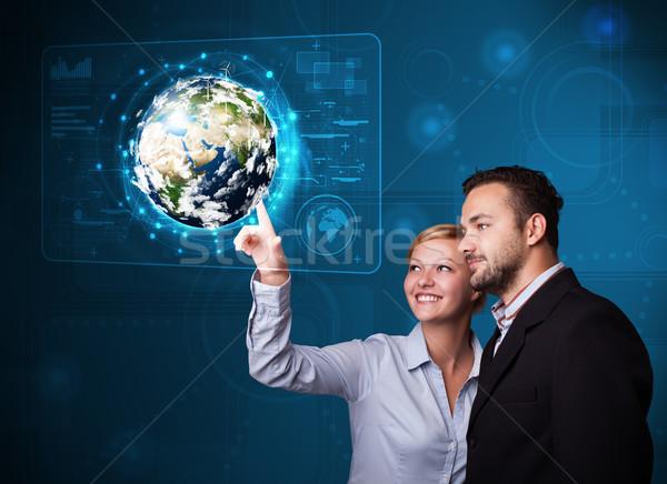 Young couple touching high-tech 3d earth panel Stock photo © ra2studio