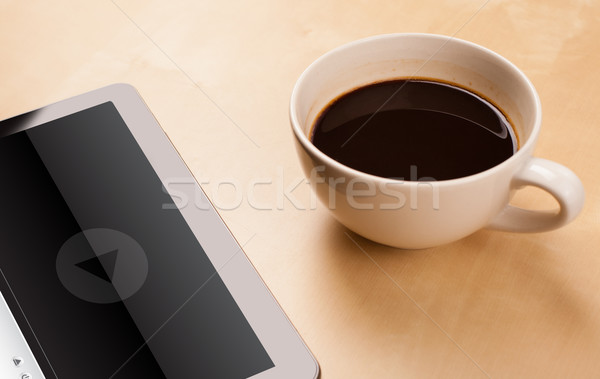 Workplace with tablet pc showing media player and a cup of coffee on a wooden work table closeup Stock photo © ra2studio