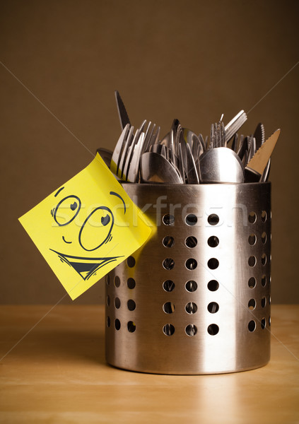 Post-it note with smiley face sticked on a cutlery case Stock photo © ra2studio