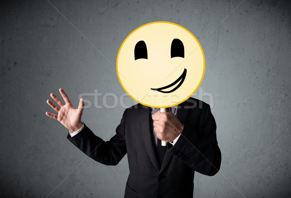 Businessman holding a smiley face emoticon Stock photo © ra2studio