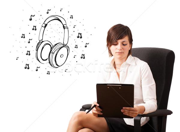 Fiatal lány bemutat fejhallgató hangjegyek izolált fehér Stock fotó © ra2studio