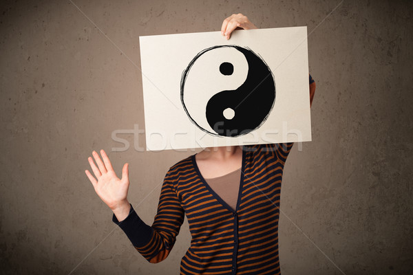 Woman holding a paper with a yin-yang on it in front of her head Stock photo © ra2studio