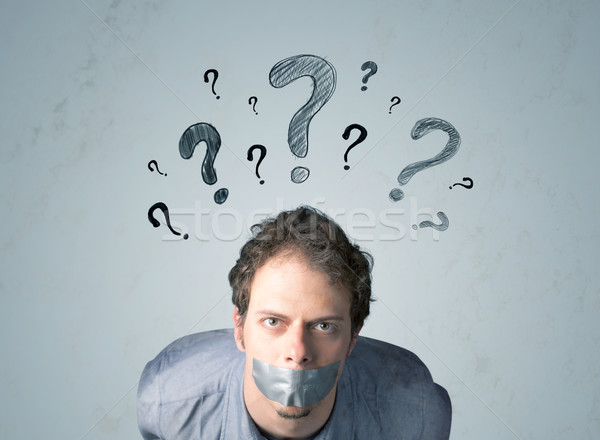 Young man with glued mouth and question mark symbols Stock photo © ra2studio