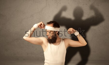 Skinny man with musculous shadow Stock photo © ra2studio