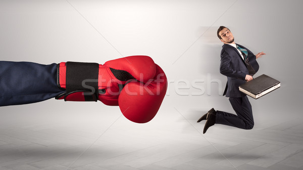 Stock photo: Giant hand gives a kick to a small businessman