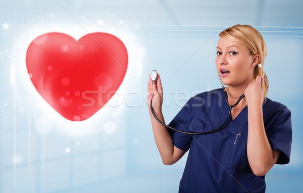Jovem enfermeira cura vermelho coração bastante Foto stock © ra2studio