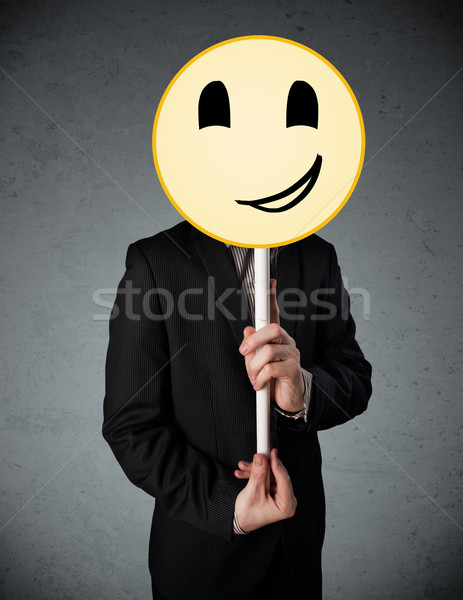 Businessman holding a smiley face emoticon Stock photo © ra2studio