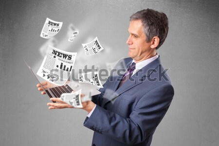 Middle aged businessman holding notebook and reading the explosi Stock photo © ra2studio
