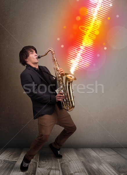 Young man playing on saxophone with colorful sound waves Stock photo © ra2studio