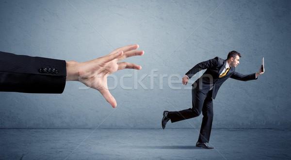 Businessman running from hand Stock photo © ra2studio