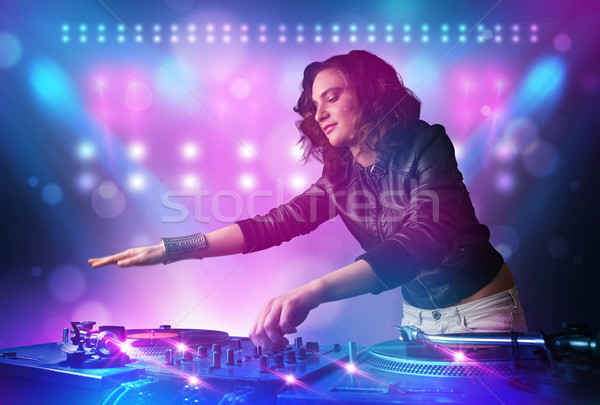 Pretty young disc jockey mixing music on turntables on stage with lights and stroboscopes Stock photo © ra2studio