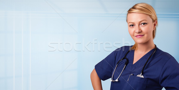 Pretty young nurse in hospital listening to empty copy space with sthetoscope Stock photo © ra2studio