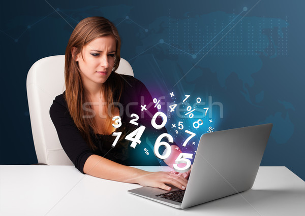 Beautiful young woman sitting at desk and typing on laptop with 3d numbers comming out Stock photo © ra2studio