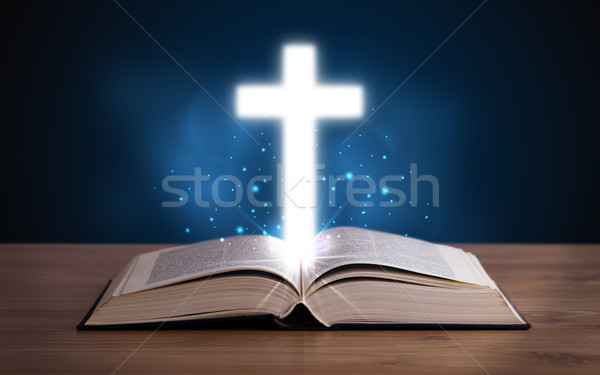 Open holy bible with glowing cross in the middle Stock photo © ra2studio