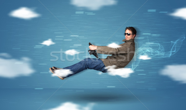 Funny racedriver young man driving between clouds concept Stock photo © ra2studio