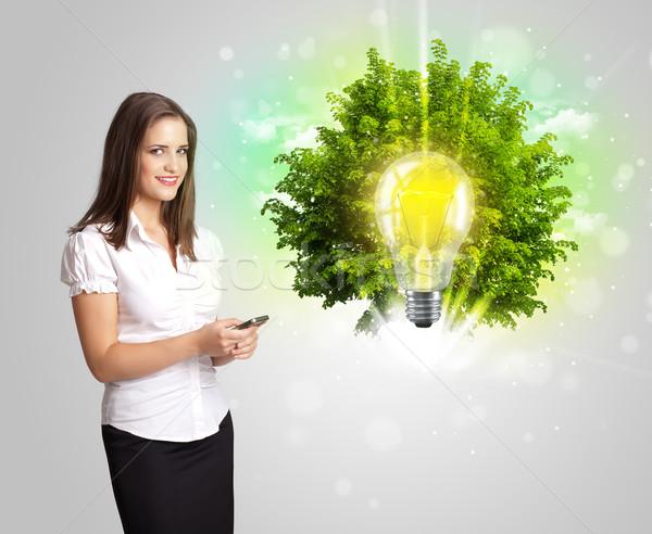Young girl presenting idea light bulb with green tree  Stock photo © ra2studio