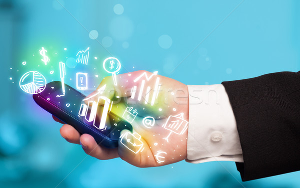 Smartphone with finance and market icons and symbols Stock photo © ra2studio