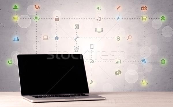 Laptop on office desk with media icons Stock photo © ra2studio