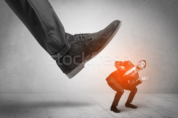Large foot stepping down small man Stock photo © ra2studio