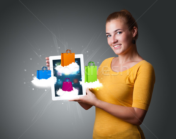 Stock photo: beautiful woman holding modern tablet with colorful shopping bags on clouds