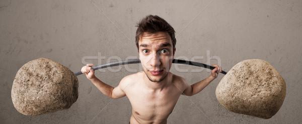 skinny guy lifting large rock stone weights Stock photo © ra2studio