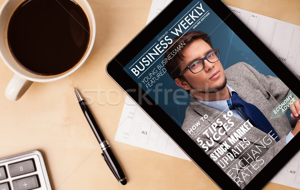 Workplace with tablet pc showing magazine cover and a cup of coffee on a wooden work table closeup Stock photo © ra2studio