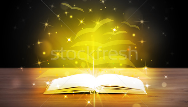 Open book with golden glow flying paper pages Stock photo © ra2studio