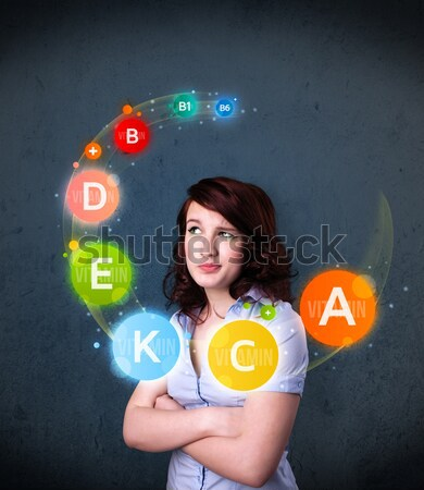 Young woman thinking with vitamins circulation around her head Stock photo © ra2studio