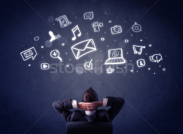 Businessman in chair with multimedia icons over his head Stock photo © ra2studio