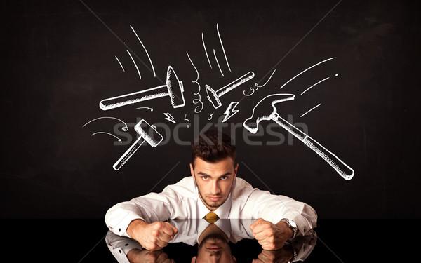 Depressed businessman sitting under hammer marks Stock photo © ra2studio