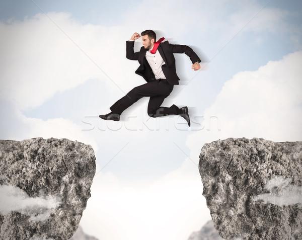 Engraçado homem de negócios saltando rochas lacuna negócio Foto stock © ra2studio