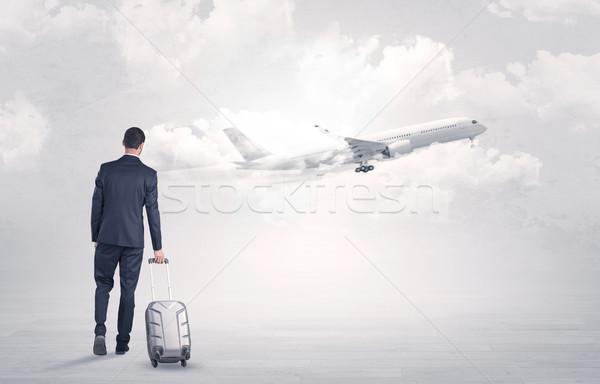 Businessman with luggage walking to airplane Stock photo © ra2studio