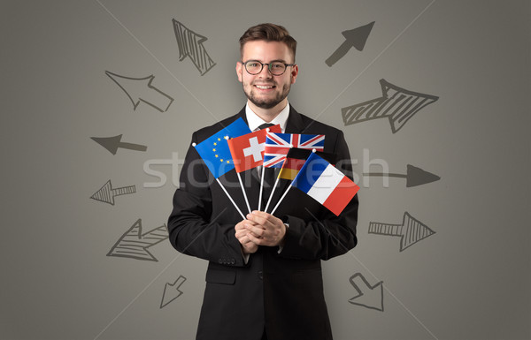 Cheerful boy standing with flag and arrows around Stock photo © ra2studio