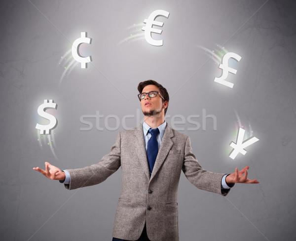 Fiatalember áll zsonglőrködés valuta ikonok kéz Stock fotó © ra2studio