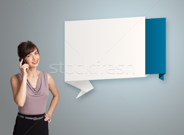 pretty young woman standing next to modern origami copy space and making phone call Stock photo © ra2studio