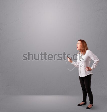 Stock photo: young lady singing and listening to music with copy space