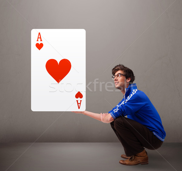 Young man holding a red heart ace Stock photo © ra2studio