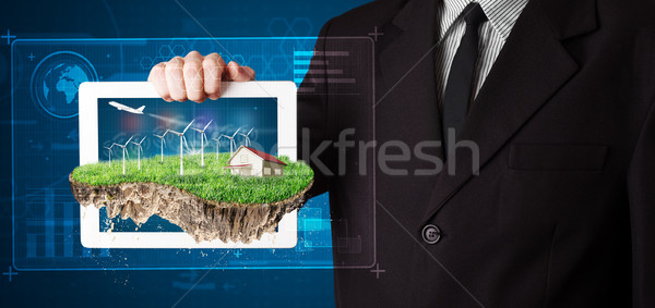 Young businessman presenting a perfect ecology land with a house and windmills Stock photo © ra2studio
