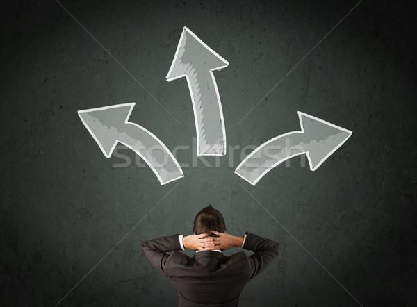 Businessman deciding with arrows above his head Stock photo © ra2studio