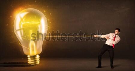üzletember húz nagy fényes izzó villanykörte Stock fotó © ra2studio