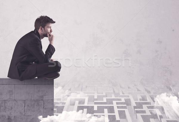 Sitting salesman on rooftop solving maze Stock photo © ra2studio