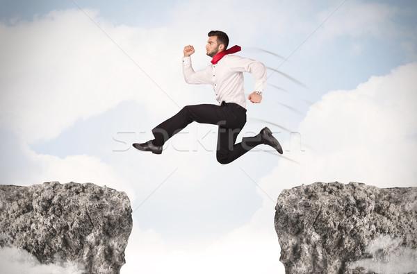 Vicces üzletember ugrik kövek hézag üzlet Stock fotó © ra2studio