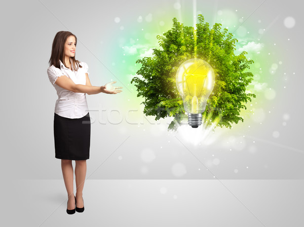 Stock photo: Young girl presenting idea light bulb with green tree