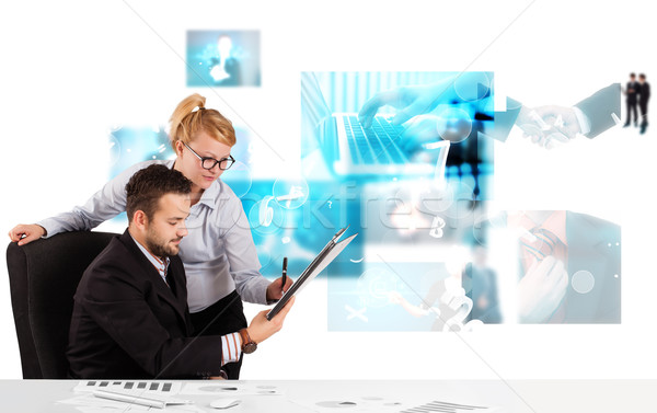 Business persons at desk with modern tech images at background Stock photo © ra2studio